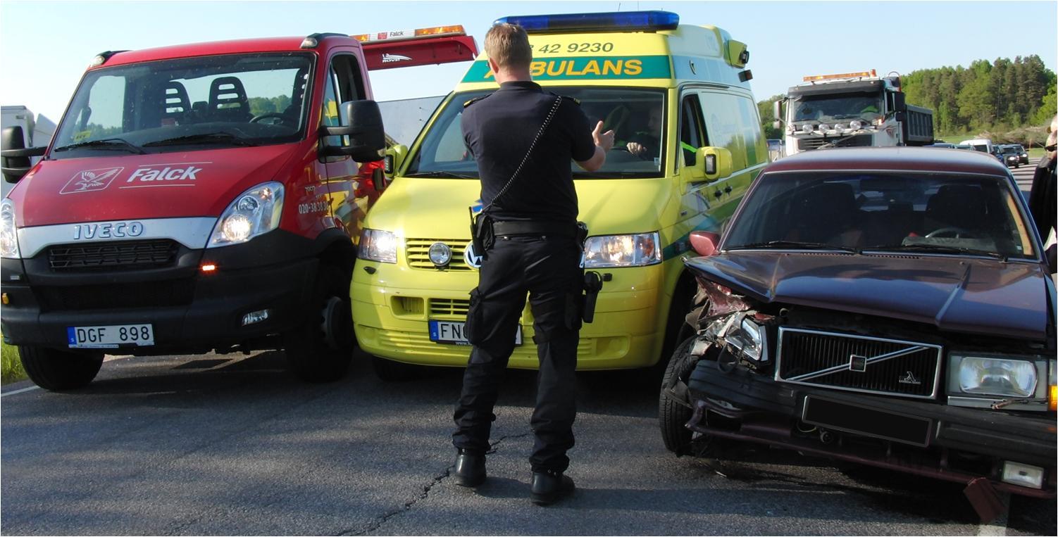 Polisen lotsar fram en förbipasserande ambulans mellan den krockade Volvon och bärgningsbilen, dit Audin snart ska vinschas upp.