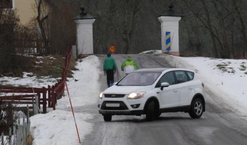 Bil backar ut på smal 50-väg med betongpelare, som omöjliggör möte