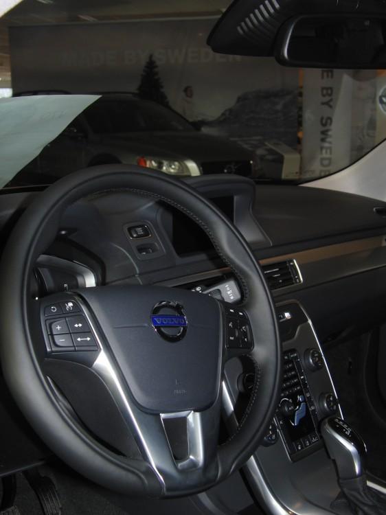 Interiör av Volvo XC70, modellår 2014, med knappar (till vänster) i ratten och (nederst) framför växelväljaren för Driver Support. Kameror och laserinstrument för City Safety finns i modulen framför backspegeln.