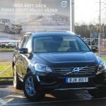 Lennart Strandbergs laborationsbil hos stop.se - Svart Volvo XC 60 AWD Summum BE Pro, modellår 2015 med Driver Support och dubbade Nokian-däck handtvättad av Rejmes rekondproffs. Parkerad framför skylt med text om däckval.
